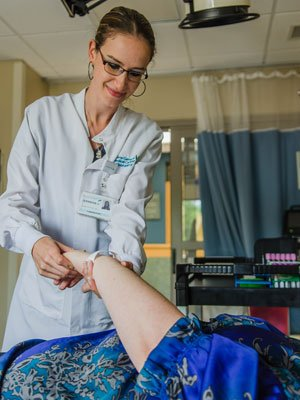 A phlebotomist prepares to take a blood sample for testing