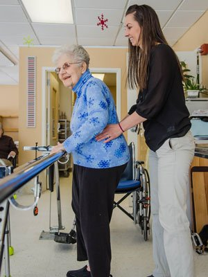 A MaineGeneral physical therapist assists a patient with strength and balance exercises