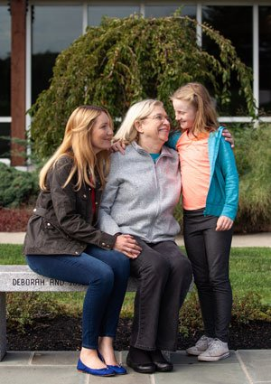 A cancer patient and her family enjoy a sunny afternoon outside the Harold Alfond Center for Cancer Care.