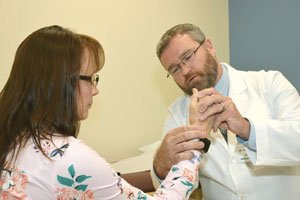 MaineGeneral Orthopaedics hand surgeon John Thaller, MD examines a patient's wrist injury