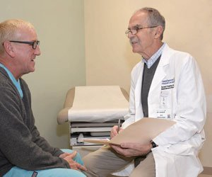 MaineGeneral rheumatologist Richard Raskin, MD consults with a patient during an office visit